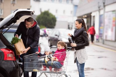 Parents pushing shopping cart with groceries and their daughters
