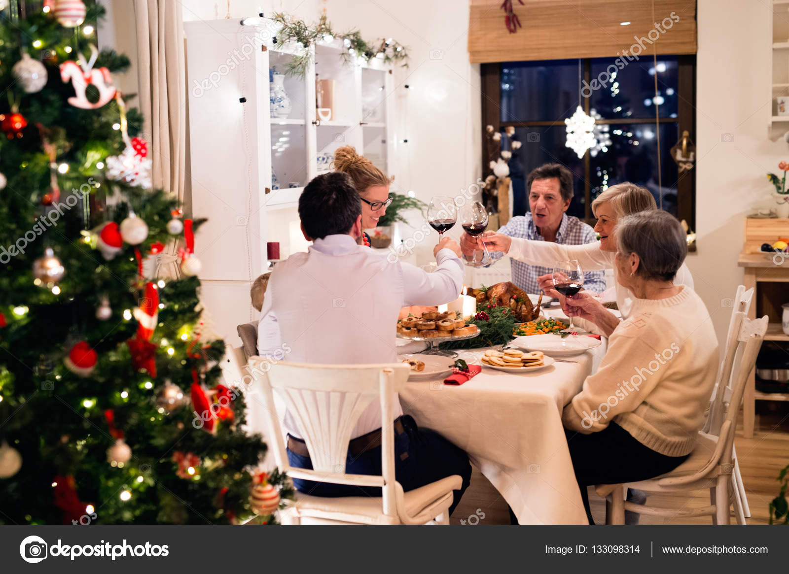 Beautiful Big Family Sitting At The Table, Celebrating Christmat Together  At Home. Illuminated Christmas Tree Behind Them. U2014 Photo By Halfpoint