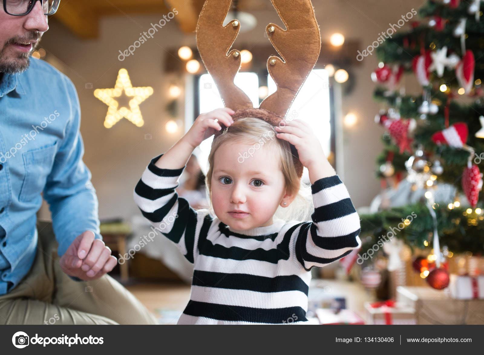 Vater mit stahlharte am Weihnachtsbaum, Rentier-Geweih tragen ...