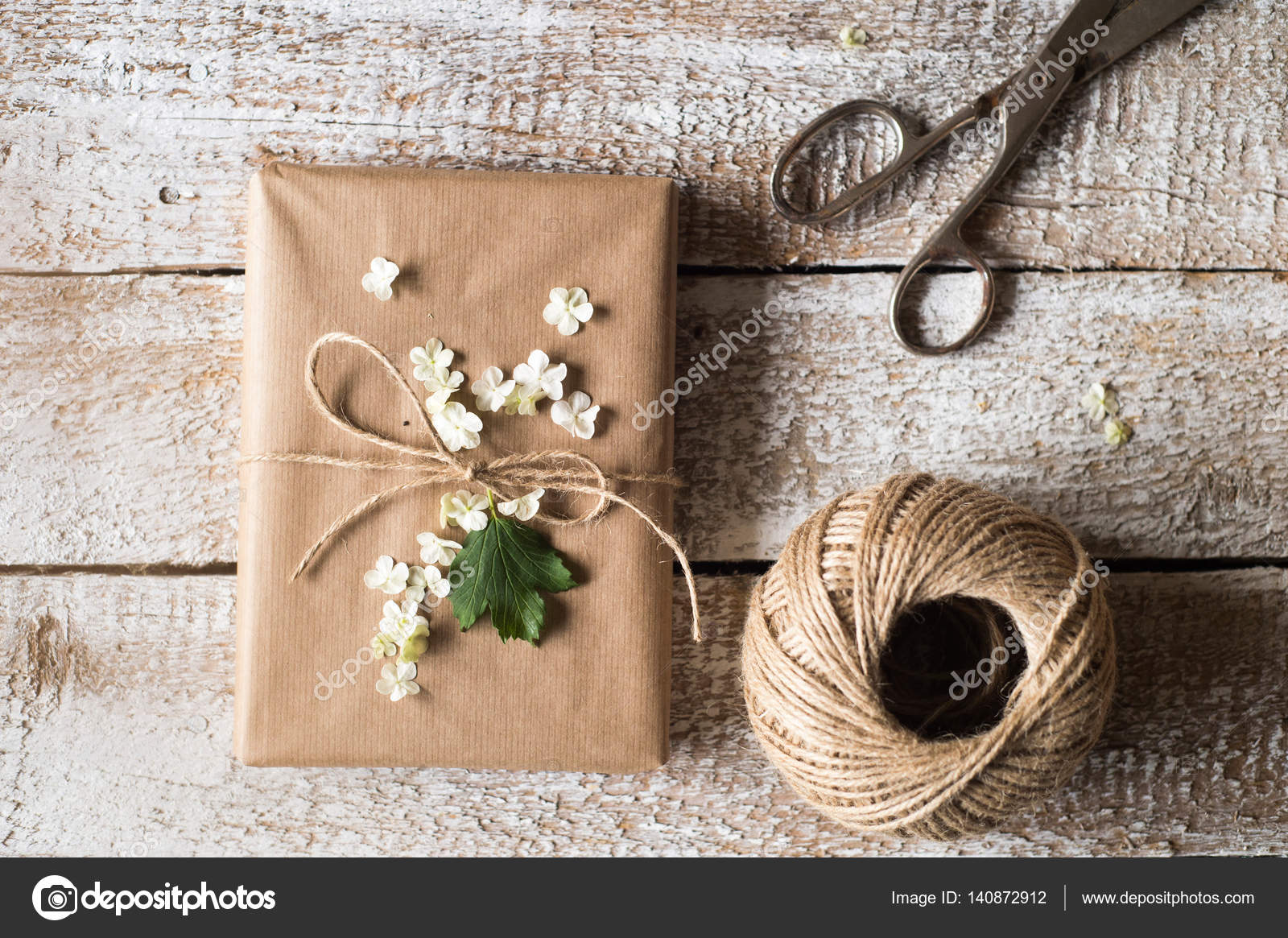 Present Wrapped In Brown Paper Lilac Flower Laid On It Studio
