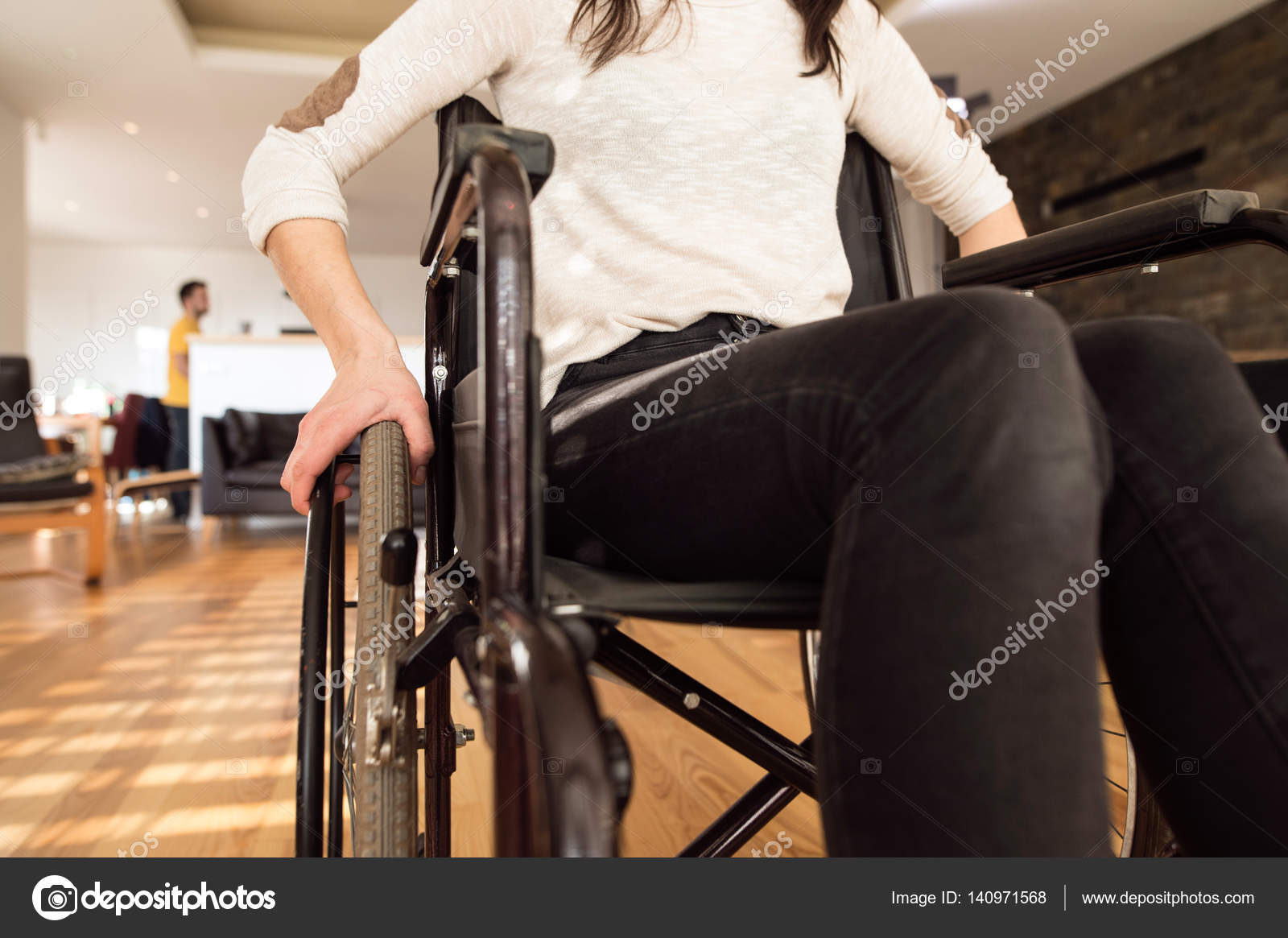 Unrecognizable disabled woman in wheelchair at home in living ro