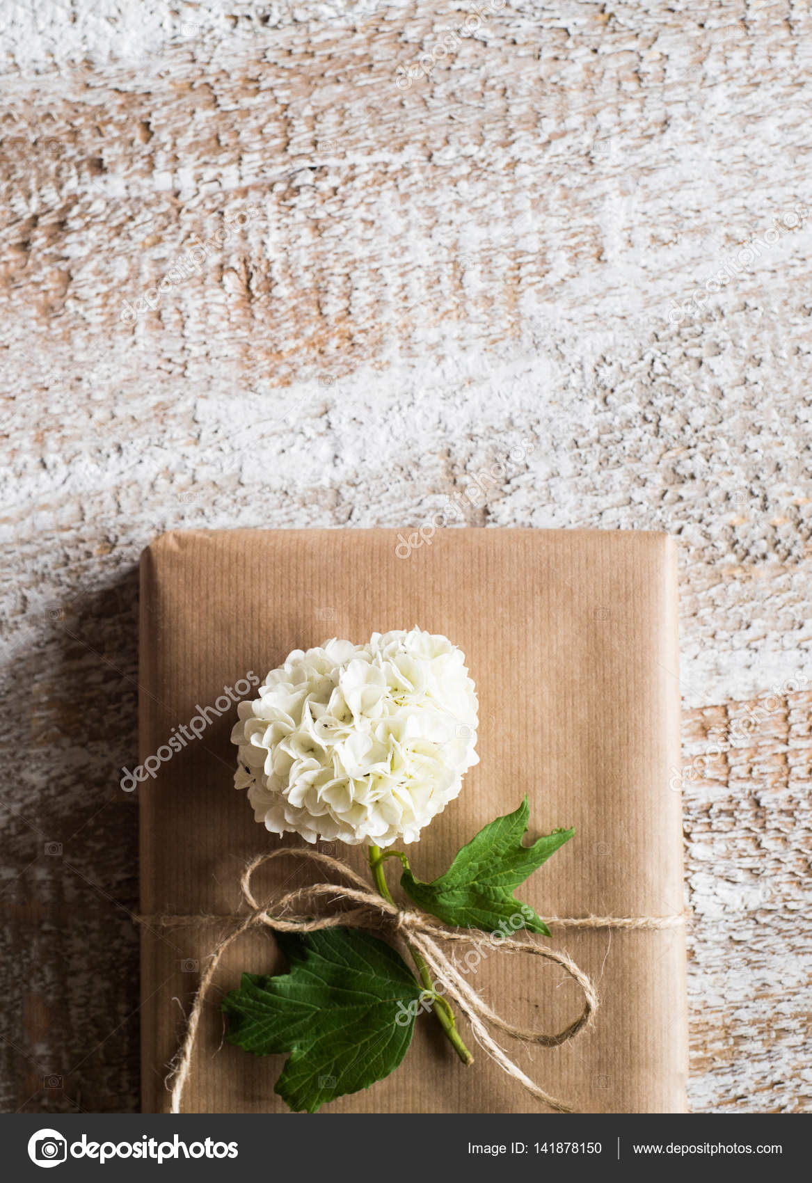 Present wrapped in brown paper lilac flower laid on it stock present wrapped in brown paper lilac flower laid on it stock photo mightylinksfo