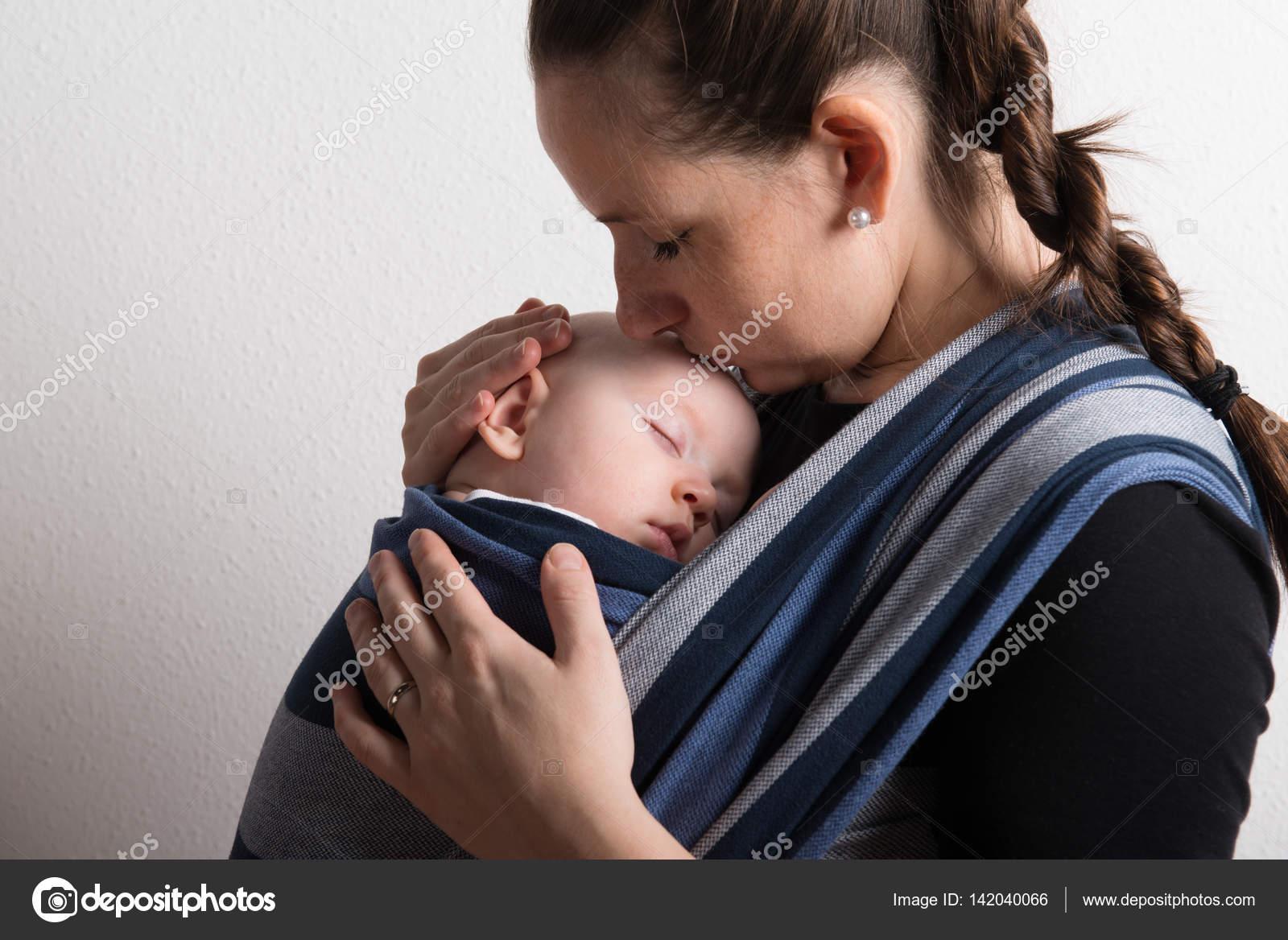 Mutter mit ihrem kleinen Sohn, der im Tragetuch schläft