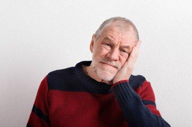 Upset senior man in red and blue sweater, studio shot.