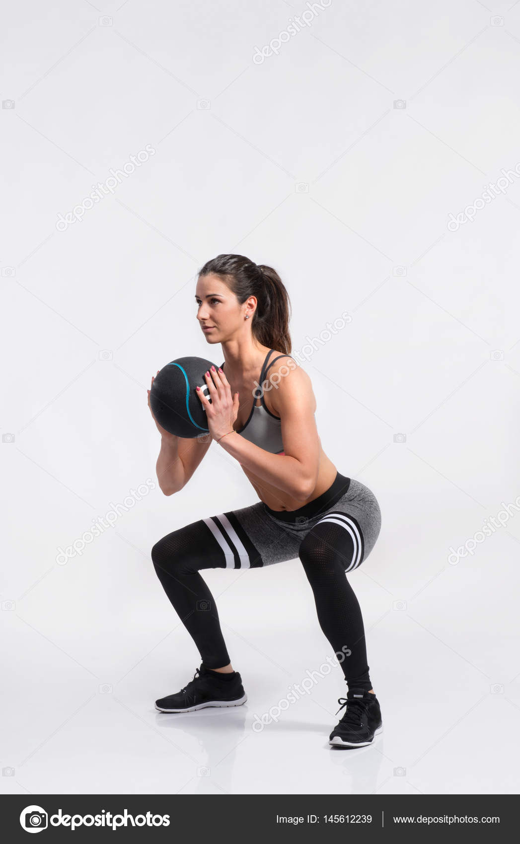 Fitness woman in sports clothing holding medicine ball, studio s