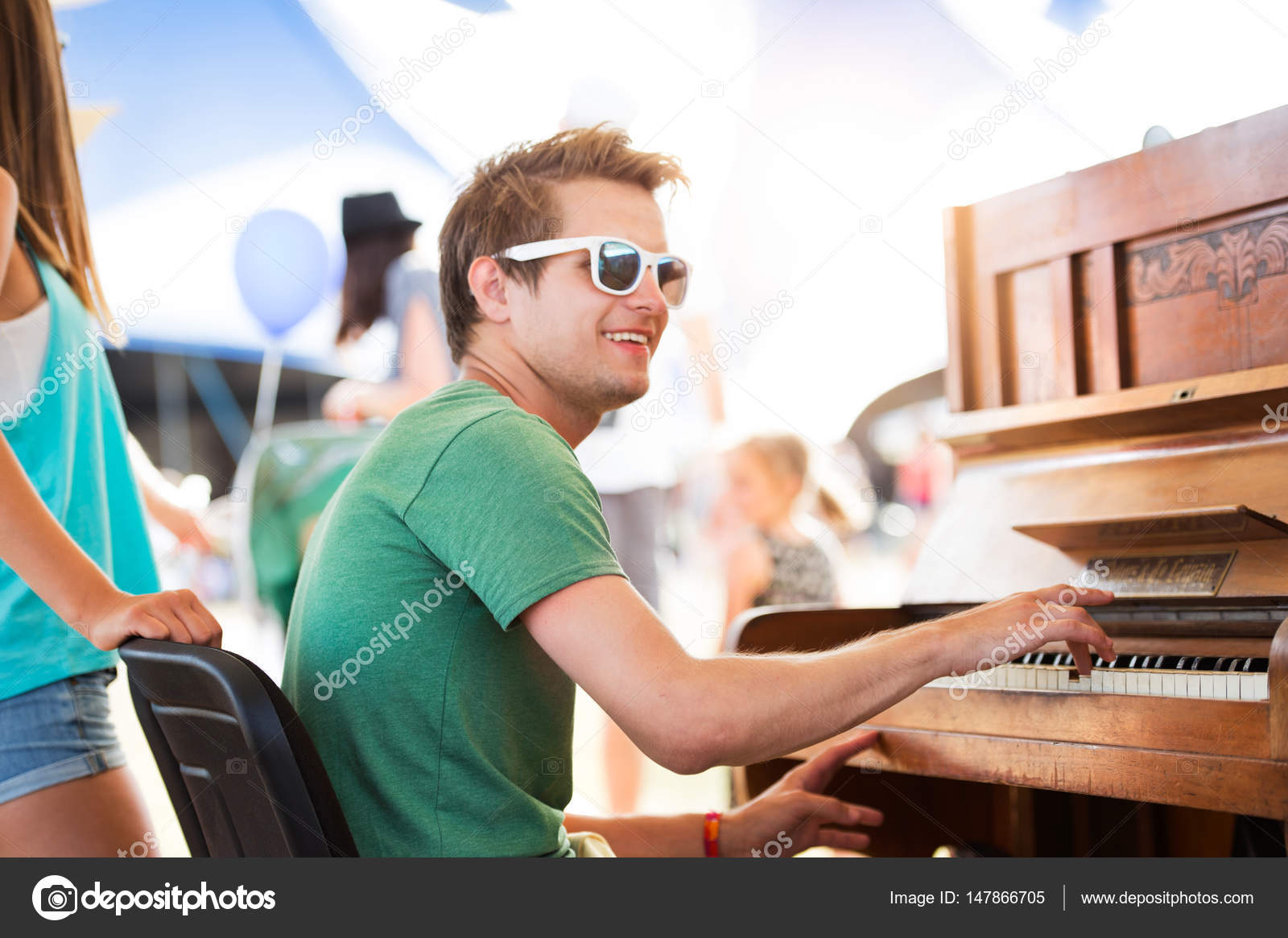 Teenage couple at summer music festival, boy plays piano