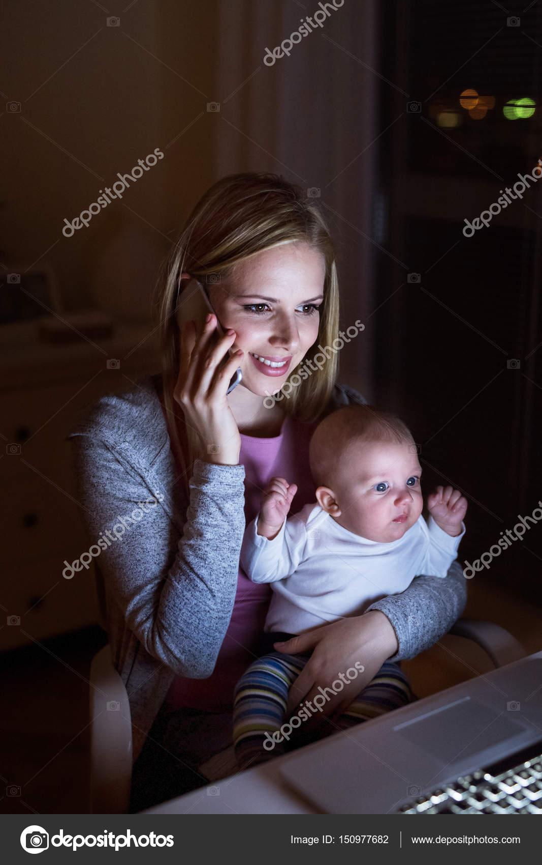 Бизнесмен с смартфон на дому с сыном на руках — стоковое фото.