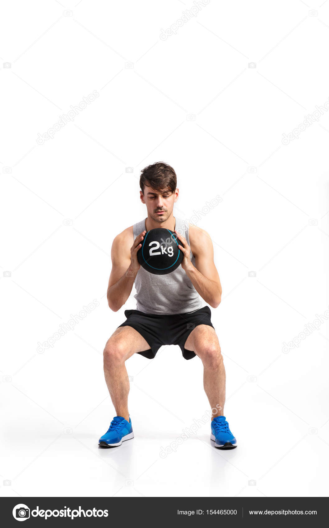 cdbb8d746f6b6 Handsome hipster fitness man in gray tank top shirt and black shorts holding  medicine ball