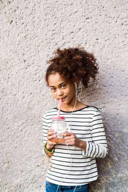 Beautiful african american girl drinking juice, listening music.