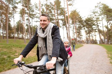 Young father and daughter together on bicycle in autumn park