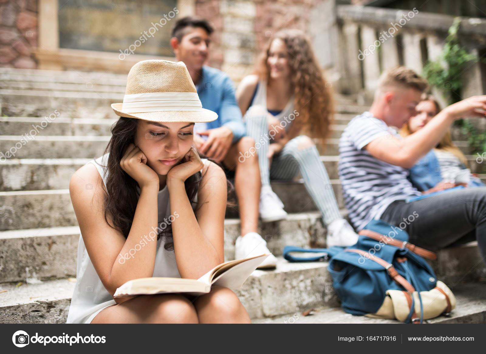 fbe1e7997 Chica estudiante adolescente sentado en los escalones de piedra ...