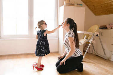 Little girl doing make-up to her attractive mother with lipstick
