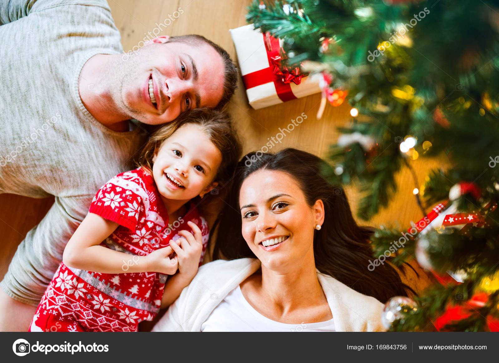 Junge Familie unter dem Weihnachtsbaum unter Geschenke liegen ...