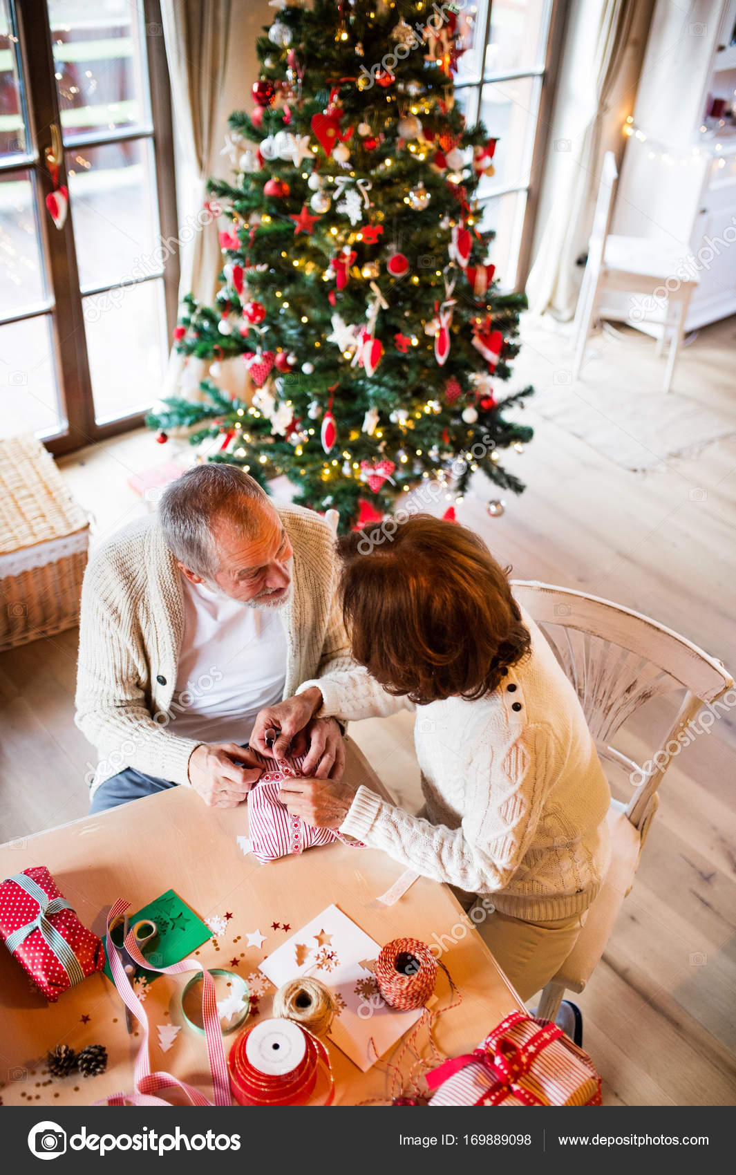 Senior couple in sweaters wrapping Christmas gifts together. — Stock ...