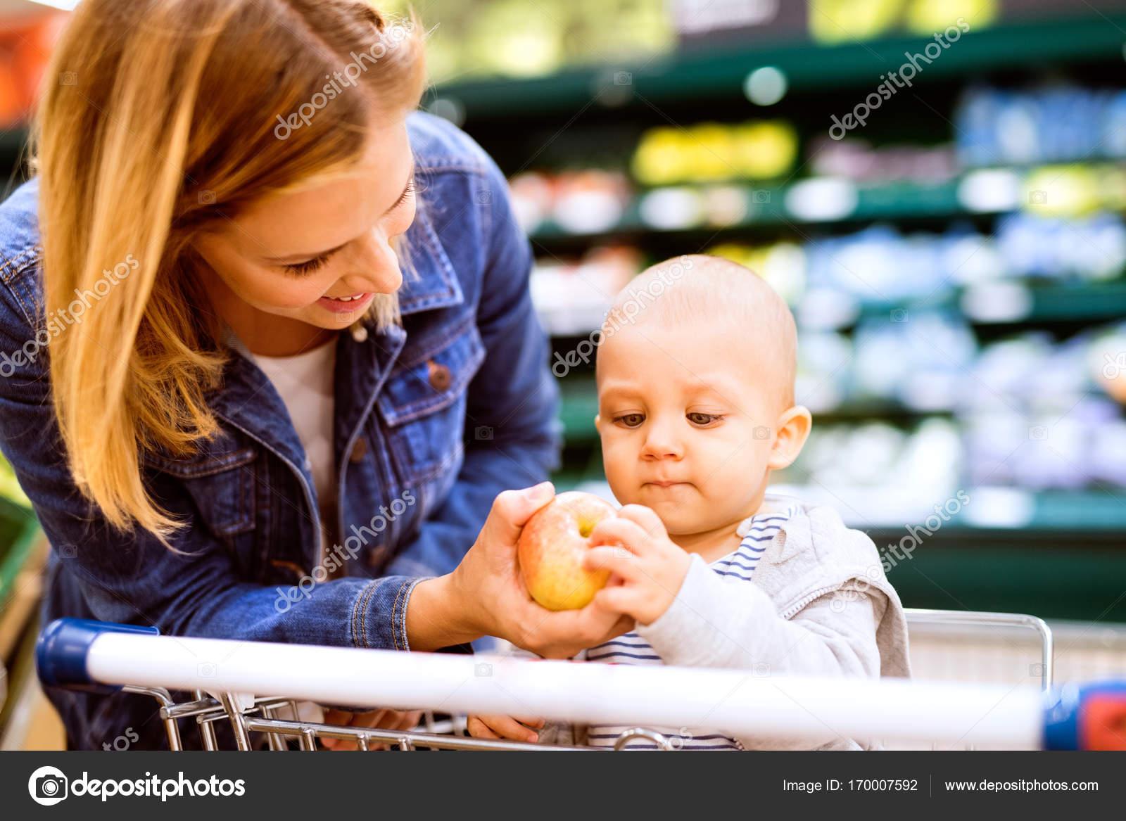 434e119506ed7c Schöne junge Mutter mit ihrem kleinen Baby-jungen im Supermarkt einkaufen.  Frau mit ihrem Sohn einen Apfel. Nahaufnahme — Foto von halfpoint