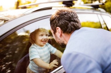 Little boy in the car, looking out of window at his father.