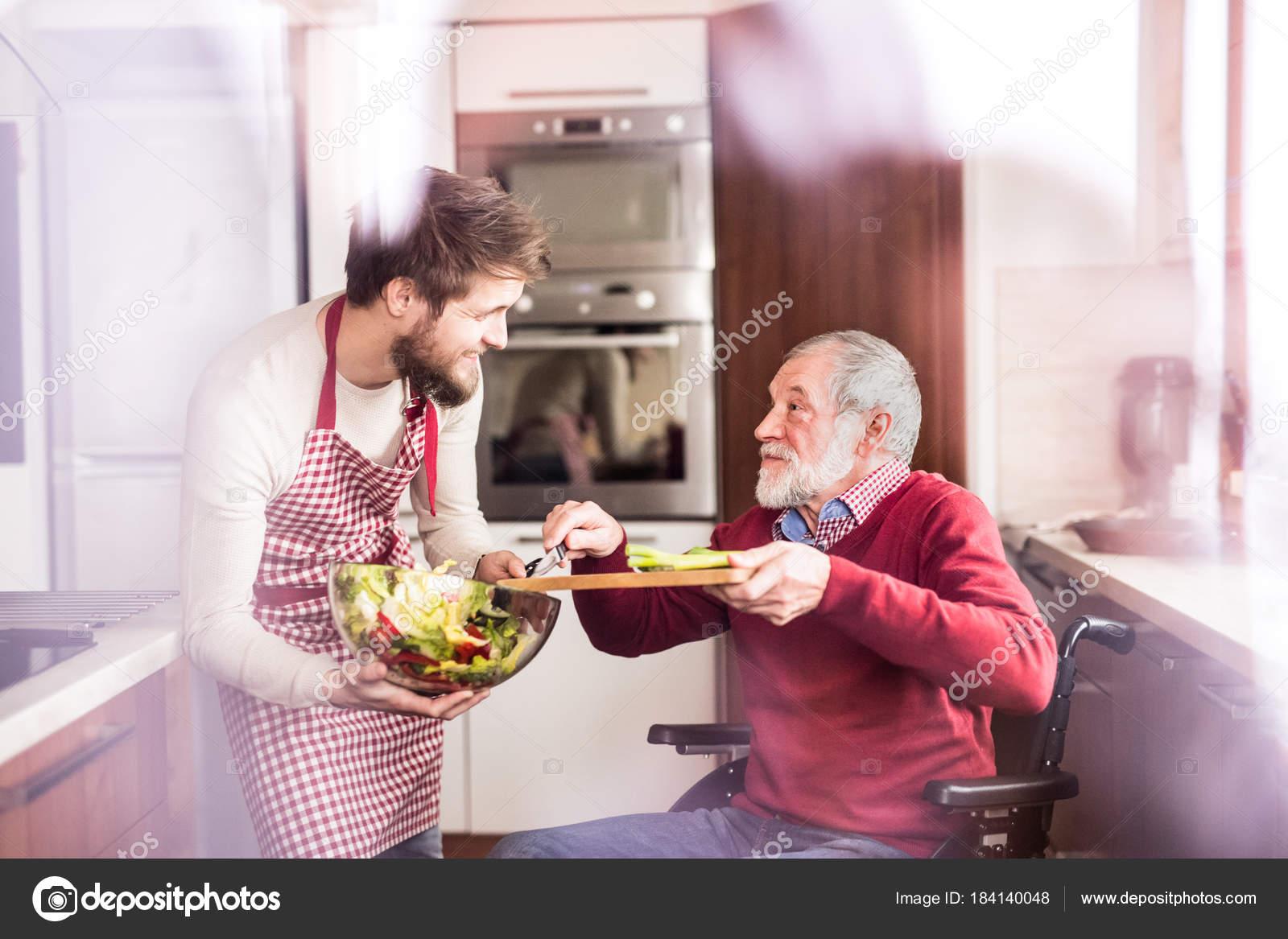 Padre hijo y senior en silla de ruedas de cocción en la cocina ...