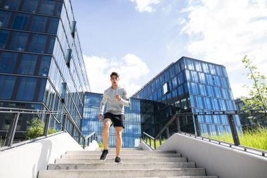 Young athlete running in front of glass buildings.