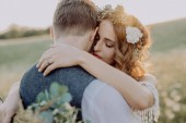 Krásná nevěsta a ženich při západu slunce v zeleni.