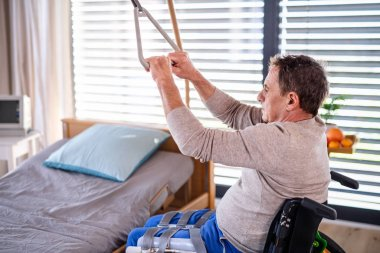 Man senior patient in wheelchair in hospital, holding onto a bed hanger.