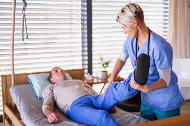 A healthcare worker and senior patient in hospital, physiotherapy.
