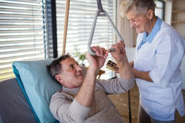 Healthcare worker helping paralysed senior patient in hospital.