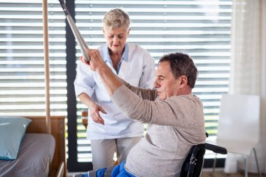 A healthcare worker helping paralysed senior patient in hospital.