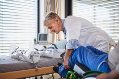 A healthcare worker and paralysed senior patient in hospital.