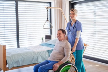 A healthcare worker and senior patient in wheelchair in hospital.