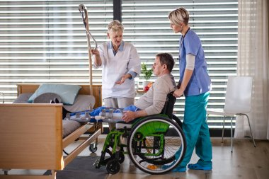 Healthcare workers and senior patient in wheelchair in hospital, talking.