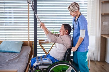 A healthcare worker and senior patient in wheelchair, physiotherapy.