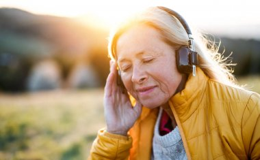Senior woman sitting outdoors in nature at sunset, relaxing with headphones.