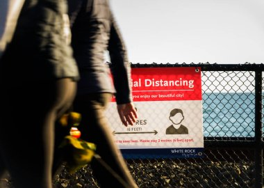White Rock, Kanada - 25 Mart 2020: Covid-19 sosyal mesafe tebligatı üzerinden yürüyen iki yaya