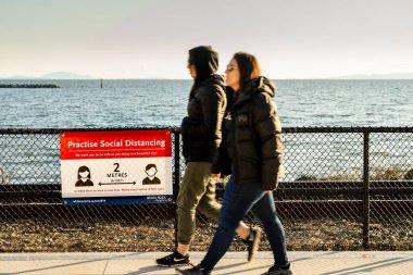 White Rock, Kanada - 25 Mart 2020: Covid-19 sosyal mesafe işaretini geçen iki yaya