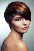 Egy gyönyörű lány, színes festett haj, divat-portré szakmai rövid haj színezése.