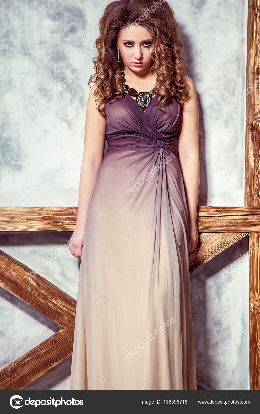 fa3110f628db Modelka s dlouhé šaty a kudrnatý účes a make-up pózuje u stěny s dřevěnou  tyč. Studio záběr– stock obrázky
