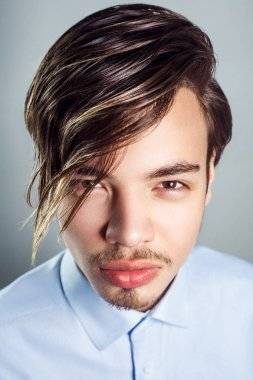 Portrait of young man with long fringe hairstyle on his eyes. studio shot. looking at camera.
