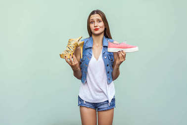 The beautiful caucasian casual girl with freckles got choosing comfortable sneakers or inconvenient but handsome high heel, thinking and looking at camera.