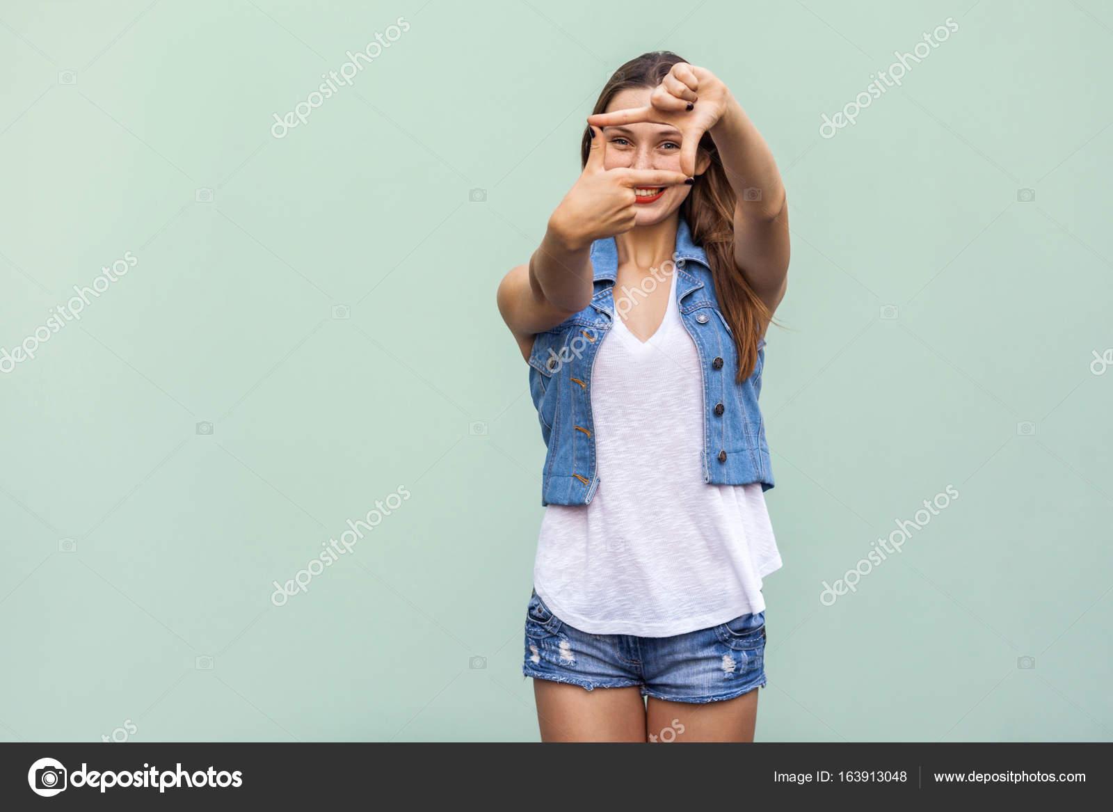 Kreative junge Frau mit Sommersprossen, macht ein Frame Geste mit ...