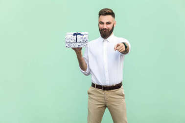Young adult bearded man, pointing at camera and holding a gift box. Studio shot on light green background