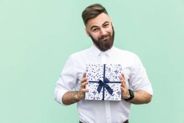 Gift with love. Interesting bearded young adult man with a gift box on light green background. Studio shot