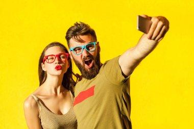 Crazy selfie. Beautiful friends macking selfie on yellow background. Studio shot