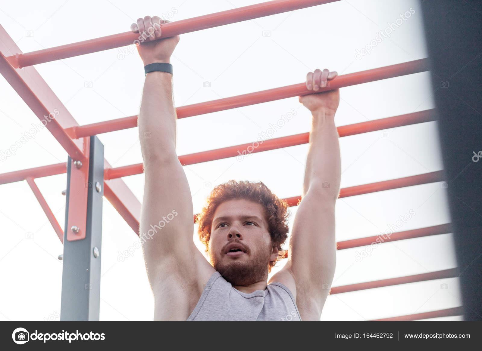 Klettergerüst Erwachsene : Junge erwachsene bärtigen rothaarige mann klettern auf bar