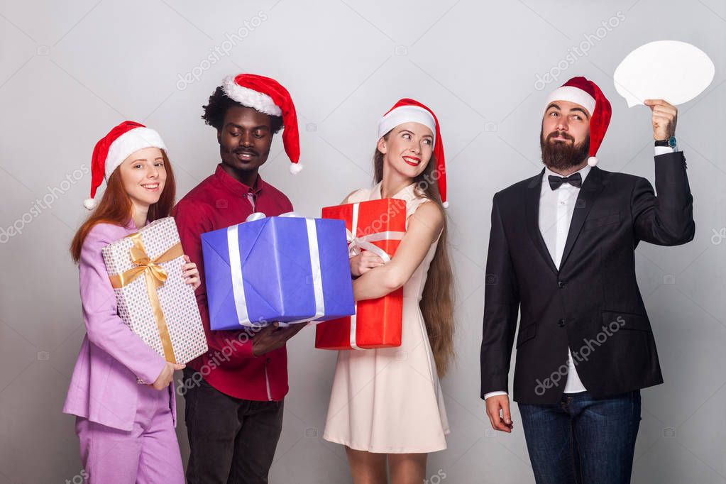 Well dressed man  looking away with puzzlement and dreaming face, her friends standing near and holding gift box. Studio shot. Gray background