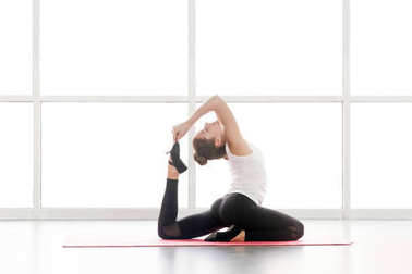 woman doing yoga while sitting in king pigeon posture in gym