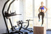 woman stepping up on cube in gym, crossfit concept