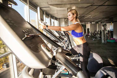 bottom view of blonde woman training on elliptical trainer in fitness club