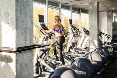 back view of blonde woman training on elliptical trainer in fitness club