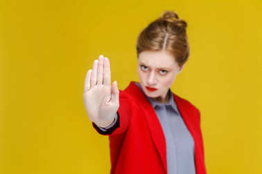seriously redhead businesswoman in red jacket showing stop hand sign on yellow background
