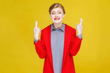 redhead businesswoman in red jacket crossed fingers and looking aside, hope and wish concept